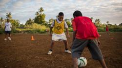 Two boys playing soccer on a dirt field