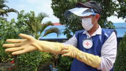 A healthcare worker putting on personal protective equipment
