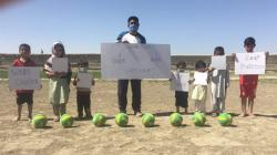Children in Balochistan holding dodgeballs and signs about covid19