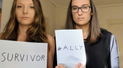 Aurélie Pankowiak and Mary Woessner holding 'survivor' and 'ally' signs