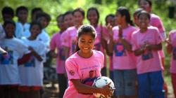 A Cambodian girl holds a soccer ball with her team behind her