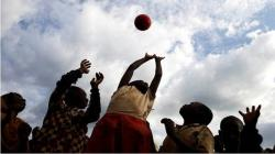 Children reaching for a ball in the air