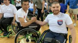 Two men in wheelchairs high fiving