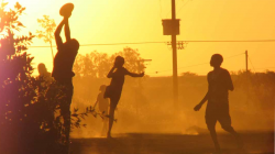 Aboriginal boys playing football in silhouette