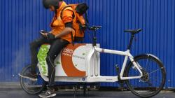 a delivery driver sits on a cargo bike