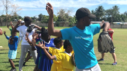 A coach and children learning to throw a baseball in Jamaica