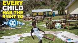 A boy kicking a football in a disaster area