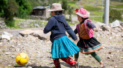 Two girls in traditional Peruvian dress running after a ball
