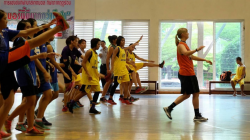 A coach leading a team of young people in a gym