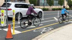 Cyclists riding in a bike lane in a city.