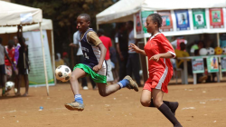 A young man and woman playing football in Kenya