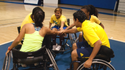 Young people playing wheelchair basketball in a huddle