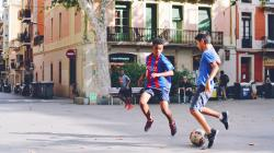 Boys playing soccer in a city