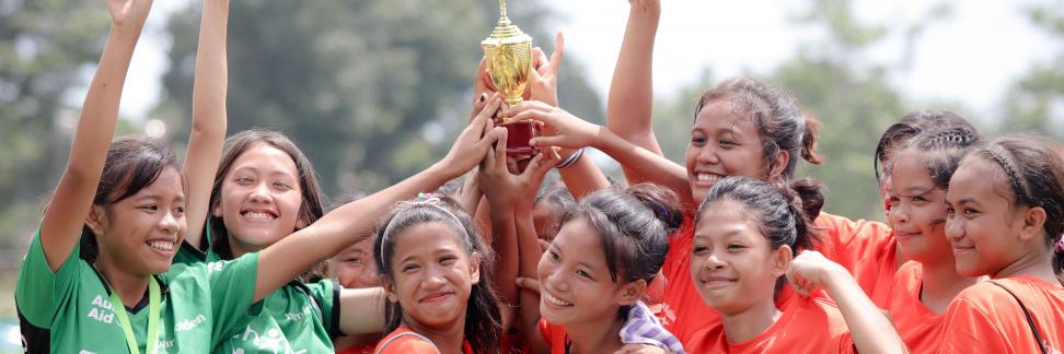 A team of girls holding a trophy